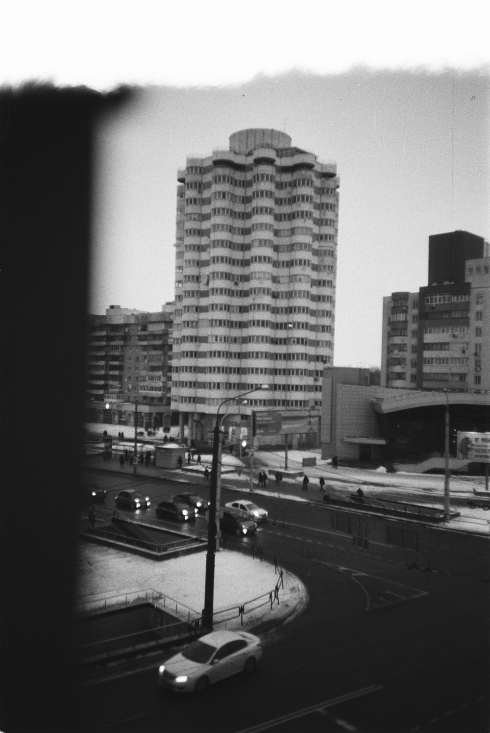 grayscale photography of vehicle beside buildings