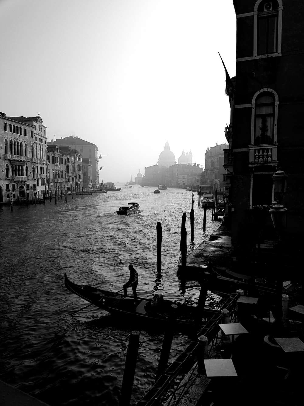 grayscale photography of body of water beside buildings