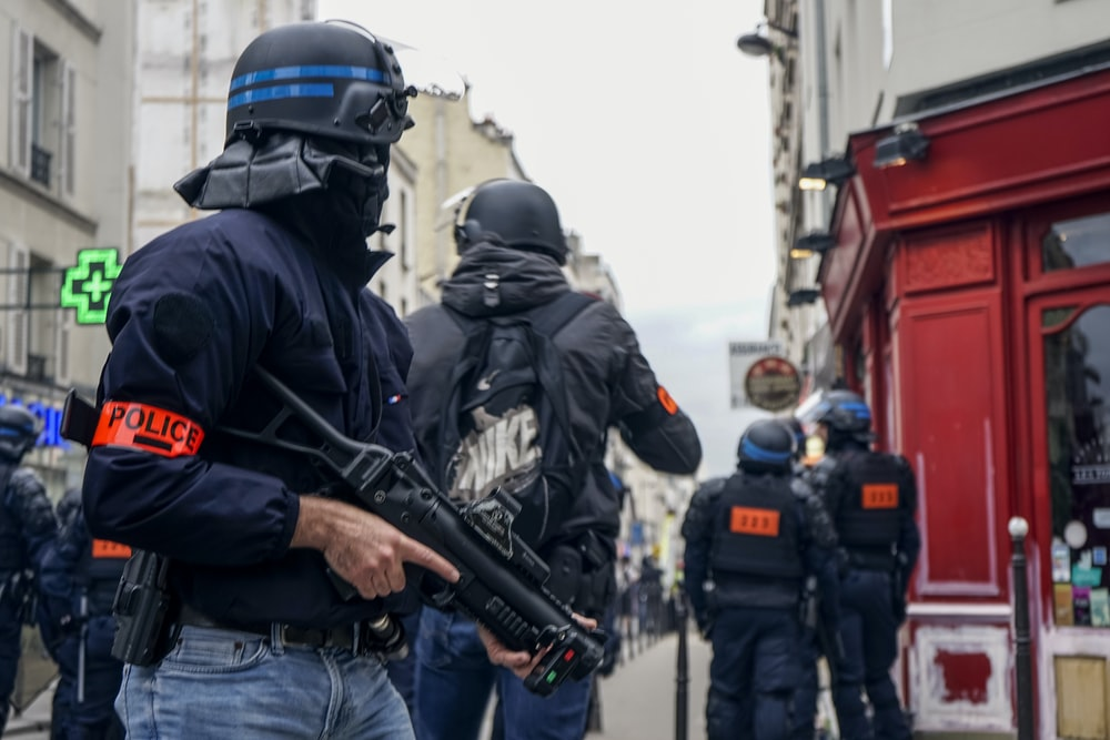 Police wearing black helmets and holding guns