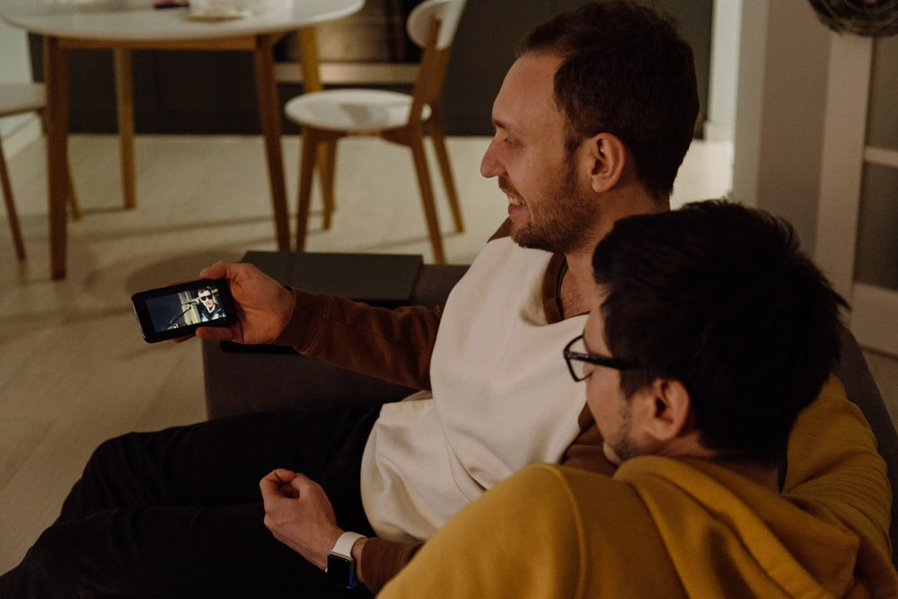 two sitting men watching from smartphone