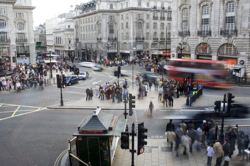 people walking at road beside concrete building