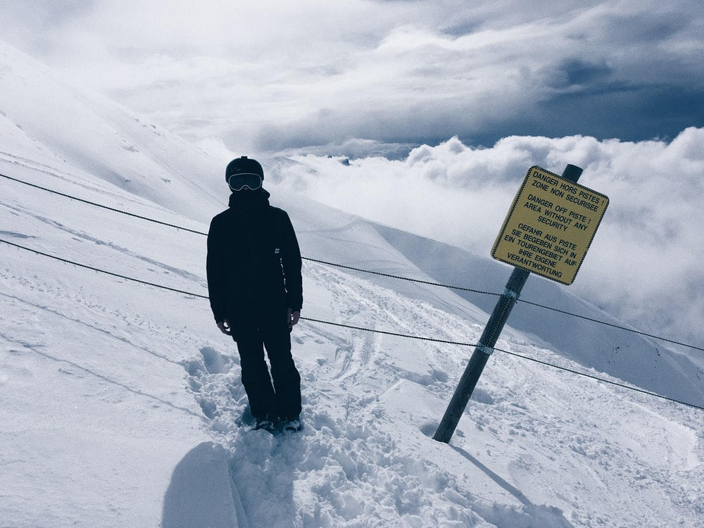 person in snowsuit standing beside sign