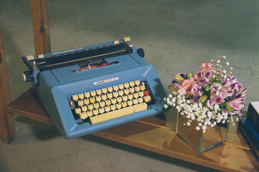 blue typewriter on brown wooden table