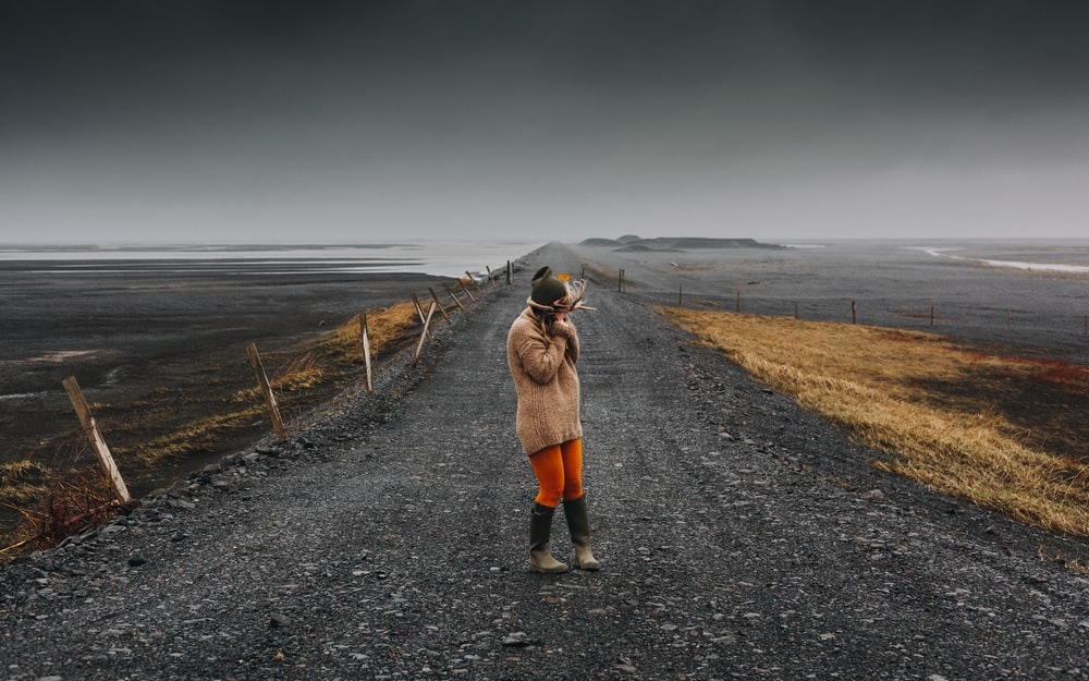 woman standing on road under cloudy sky