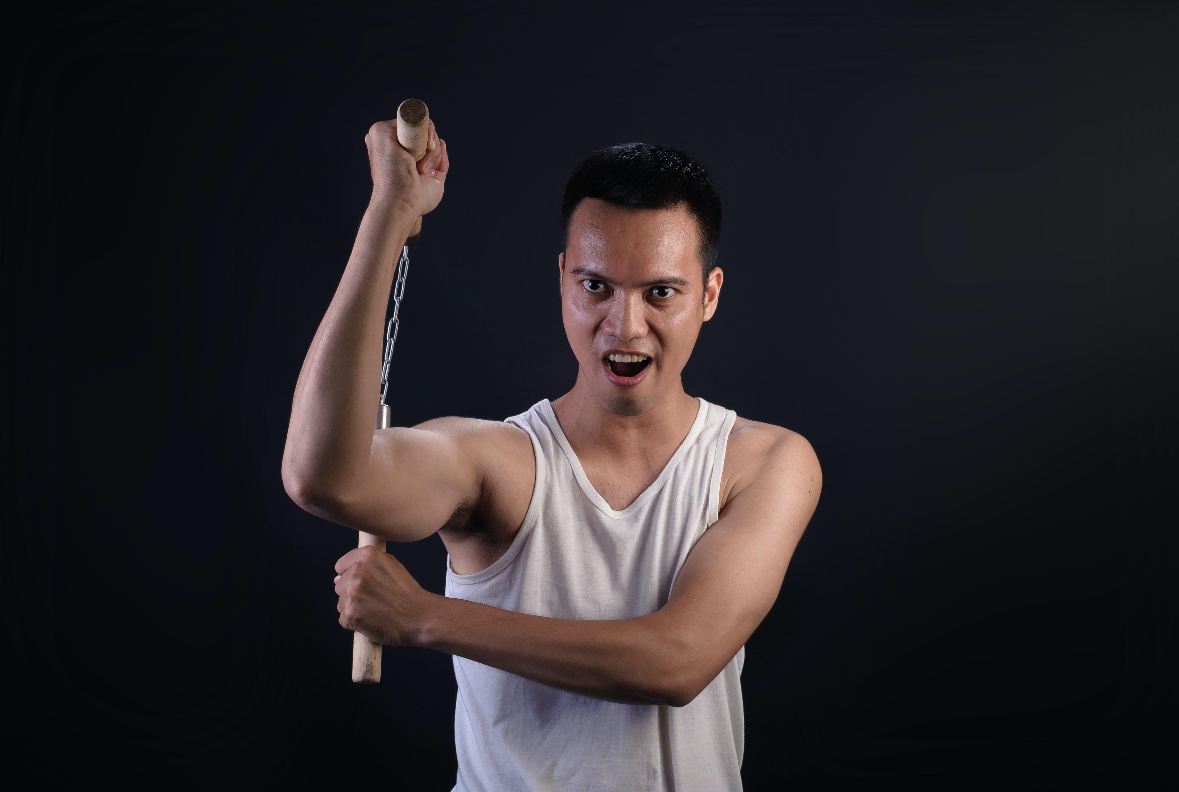 man holding brown nunchaku