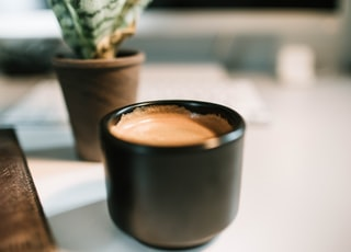 black ceramic mug filled with coffee on selective focus photography