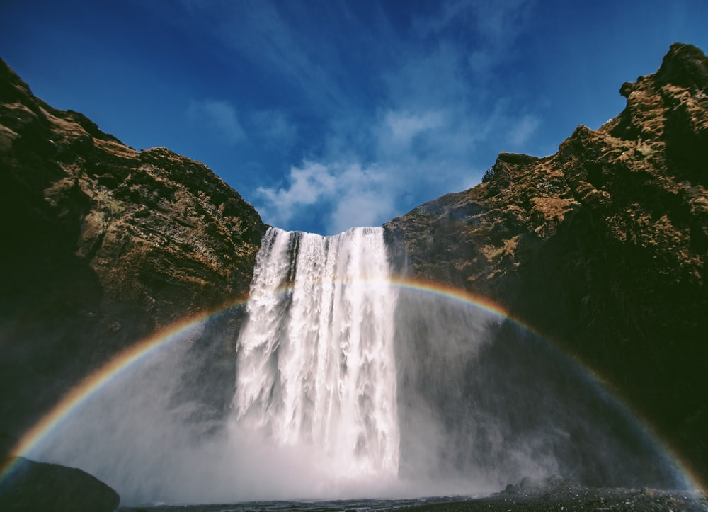low angle photography of waterfalls with rainbow during daytime