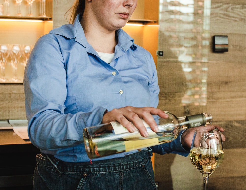 woman holding wine bottle and putting wine on wine glass