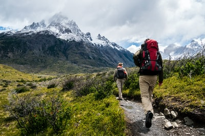 two person walking towards mountain covered with snow hiking teams background