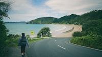person walking beside road