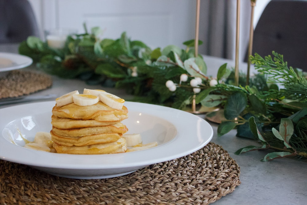 pile of pancakes on white plate near green leaves