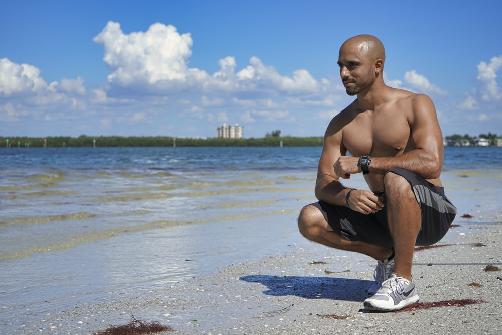 man sitting down beside seashore