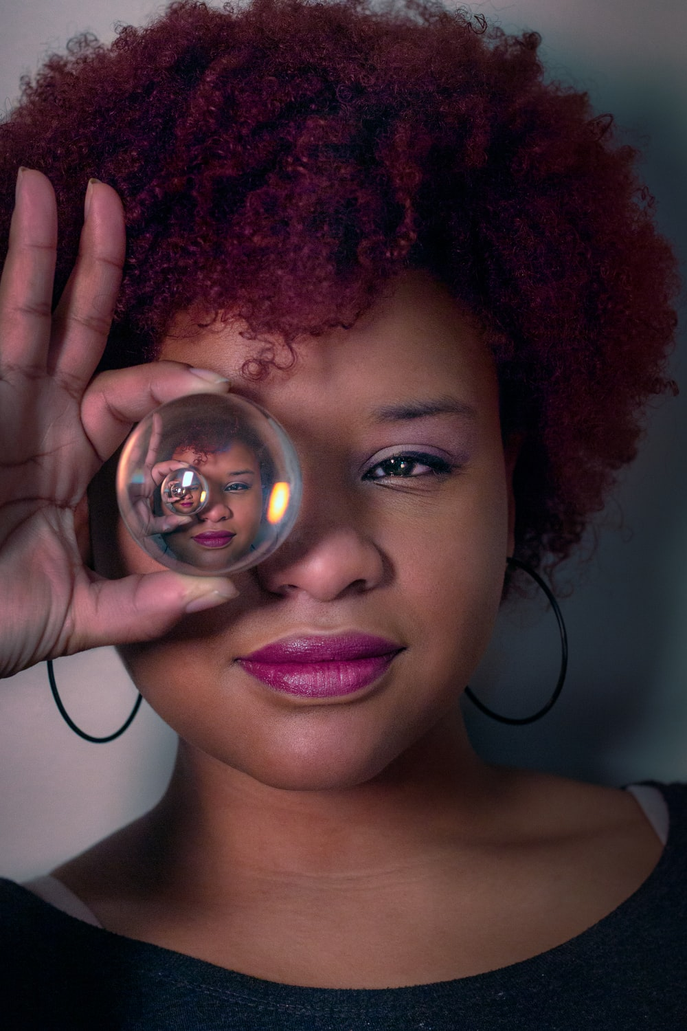 woman holding covering right eye with clear glass ball