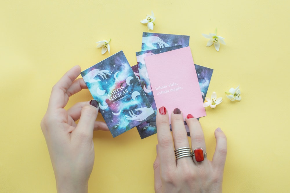 person holding blue and pink books