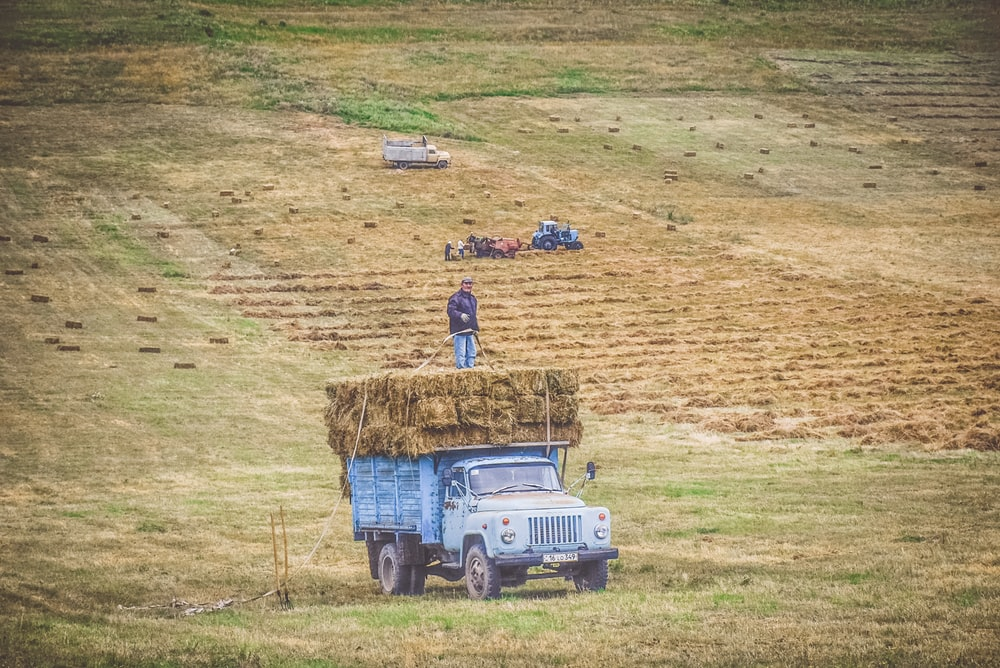 teal farm truck carrying hay