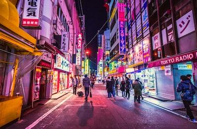 people walking between city building tokyo teams background