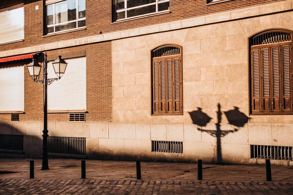 shadow of lamp post beside building during daytime