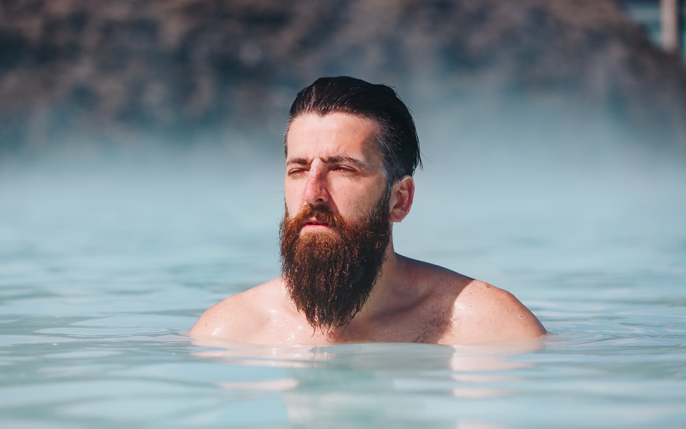 man dipping in body of water