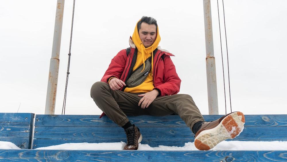 man sitting on blue wooden rail