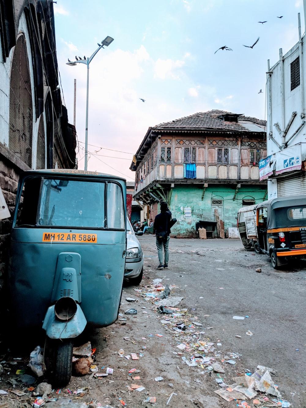 gray autorickshaw parked beside footpath road