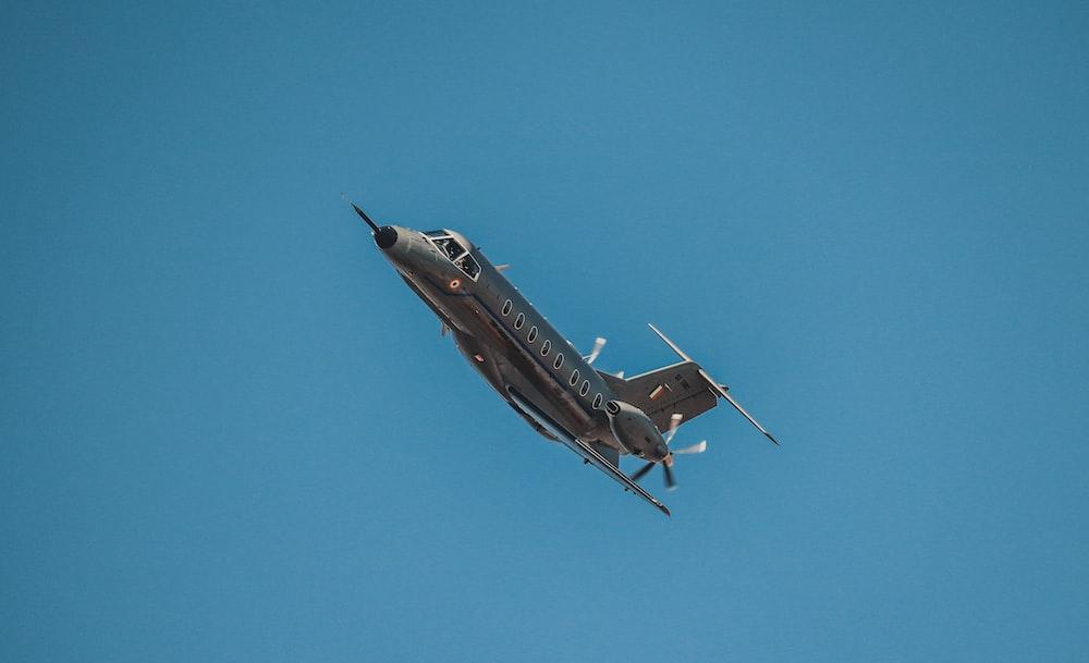 grey plane flying on sky