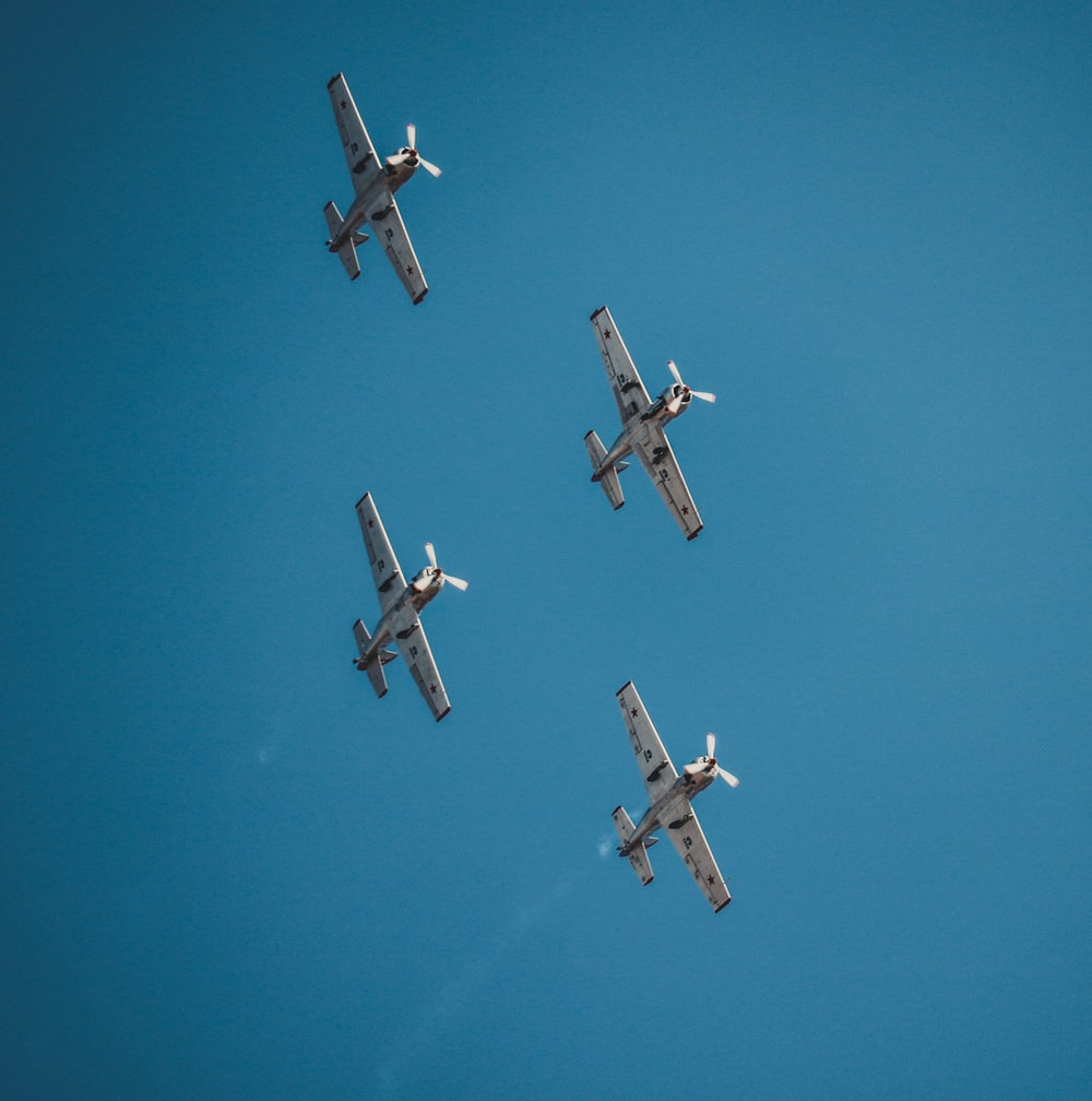 four airplane under clear blue sky during daytime
