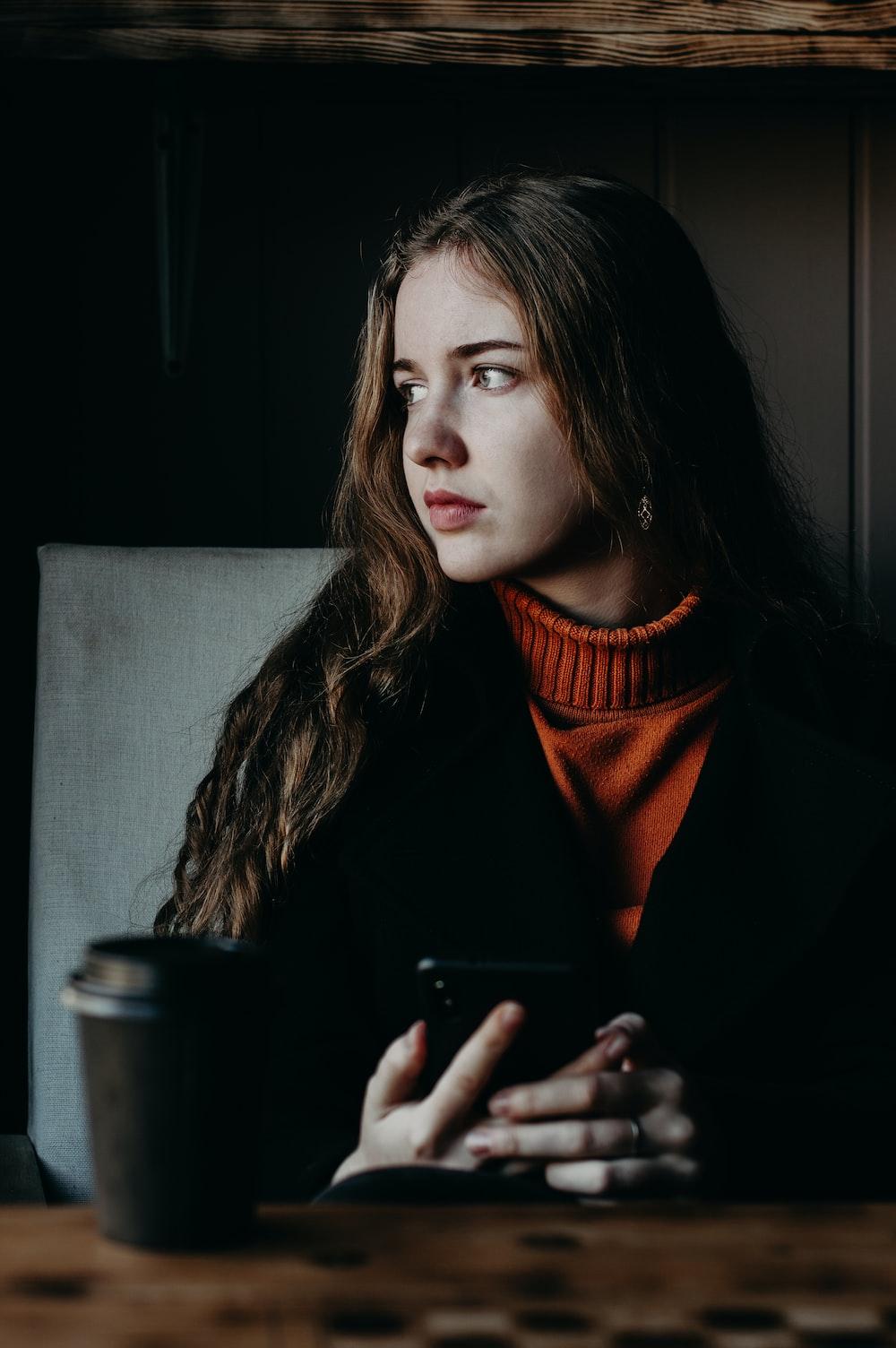 woman wearing black jacket holding smartphone