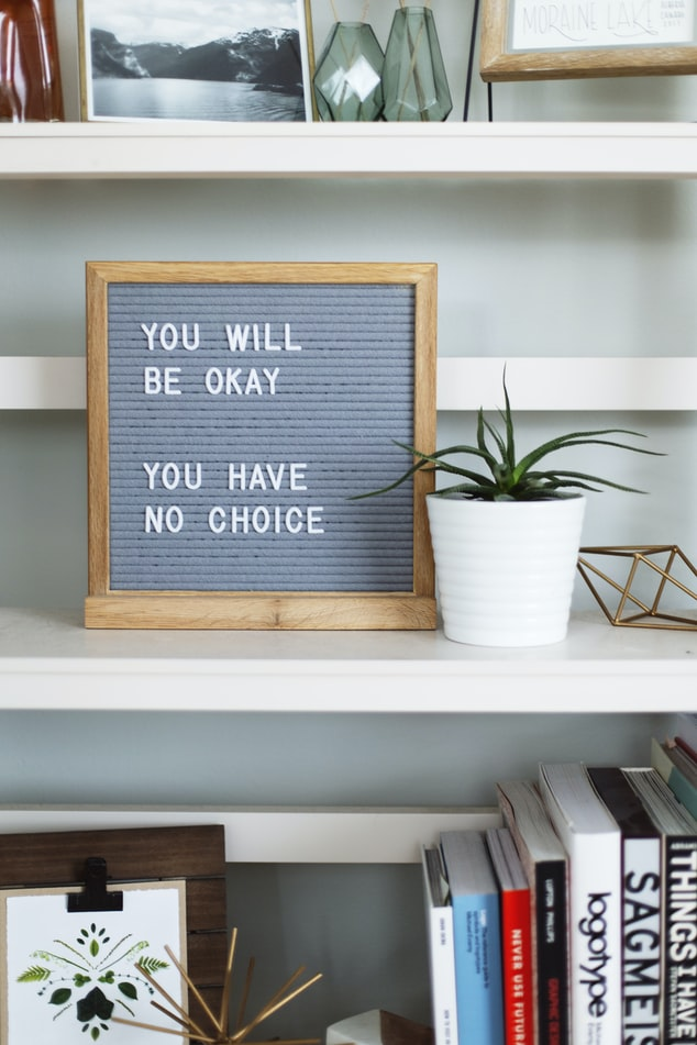 "A photo of a letterboard on a bookshelf that says ""you will be okay, you have no choice."""