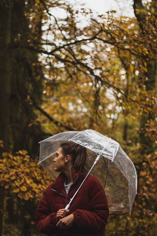 woman holding umbrella under tree