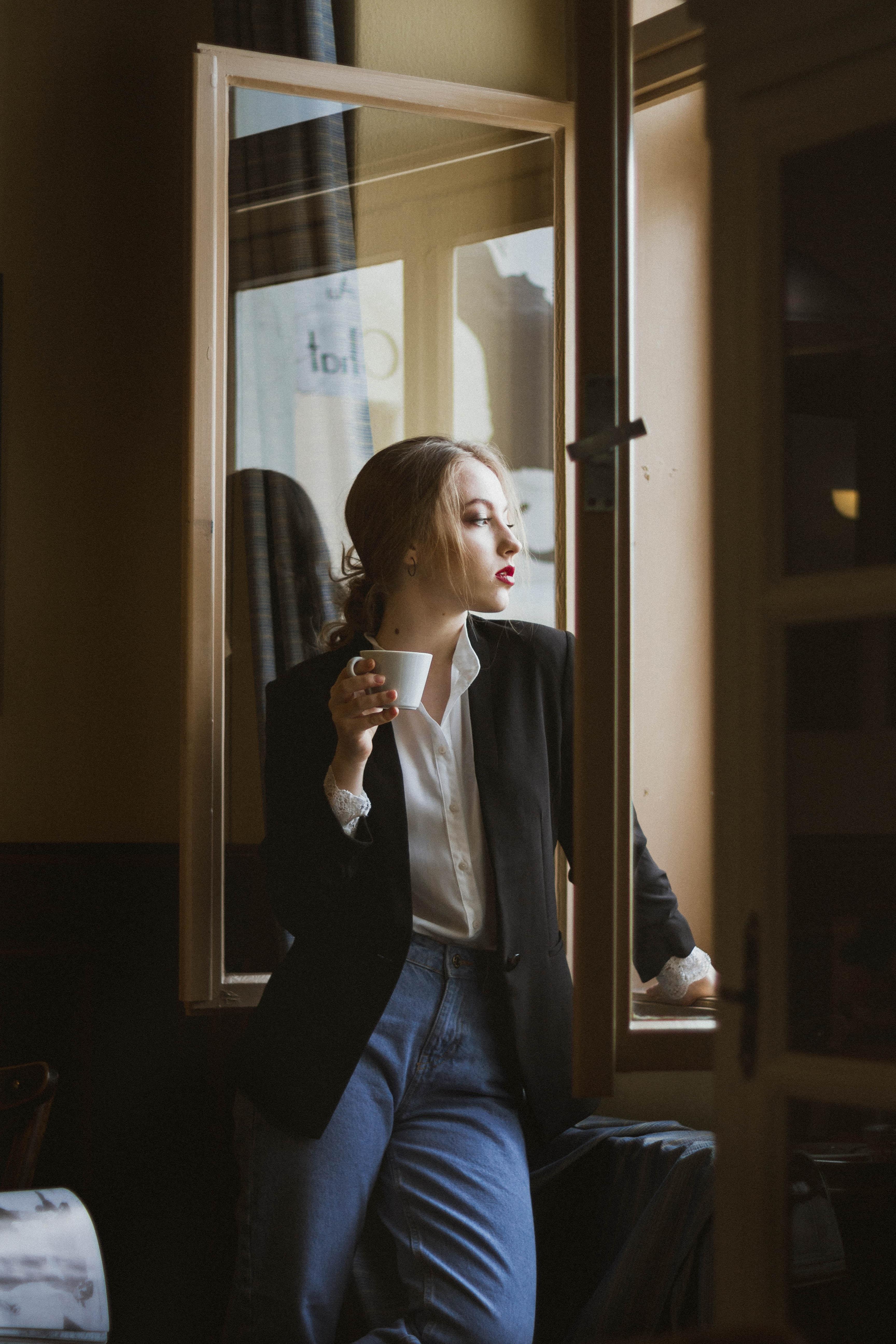 woman having coffee standing beside open window