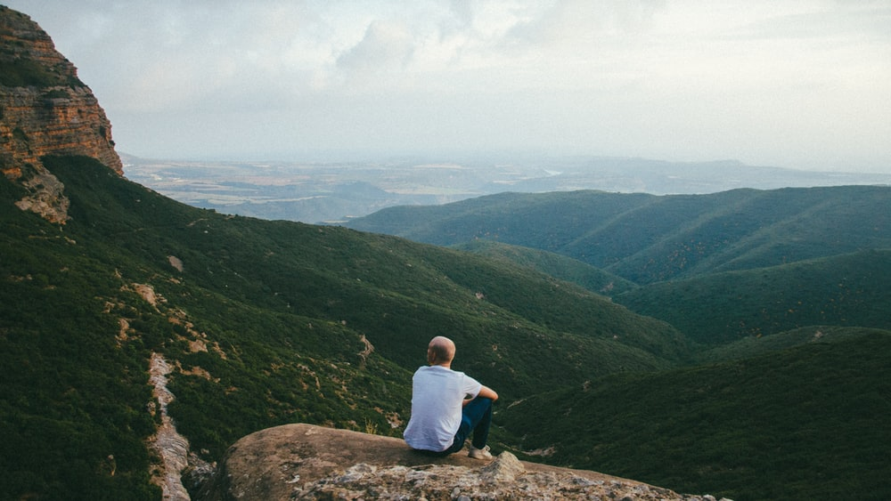 person sitting on the edge of a cliff over looking mountains during daytime