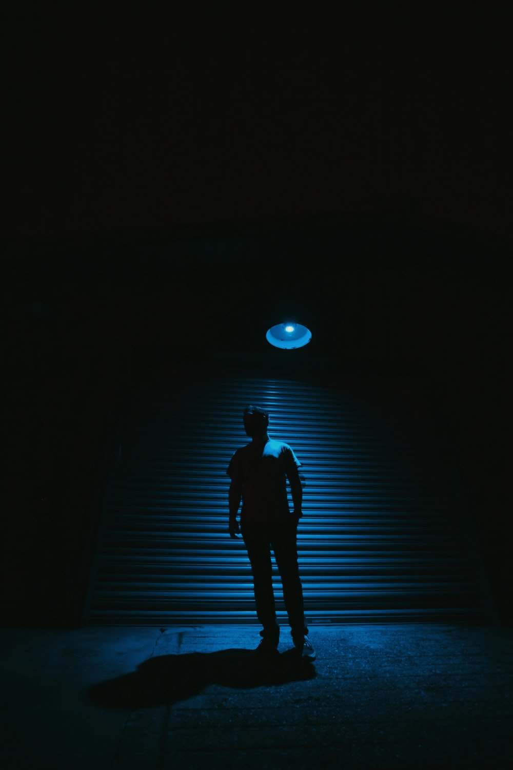 person standing near roll-up door with light turned-on