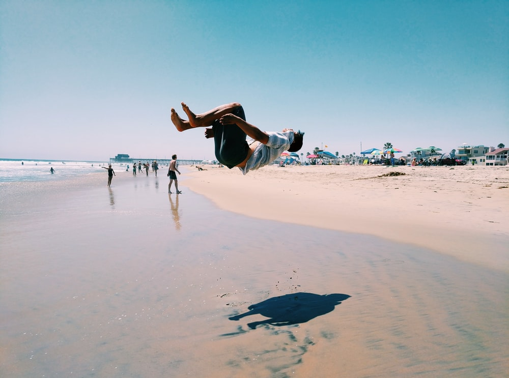 man back flipping in seashore during daytime