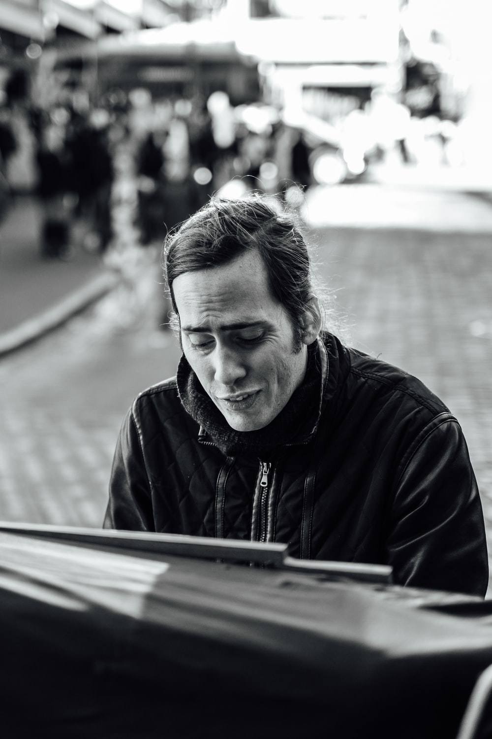 grayscale photography of man playing piano
