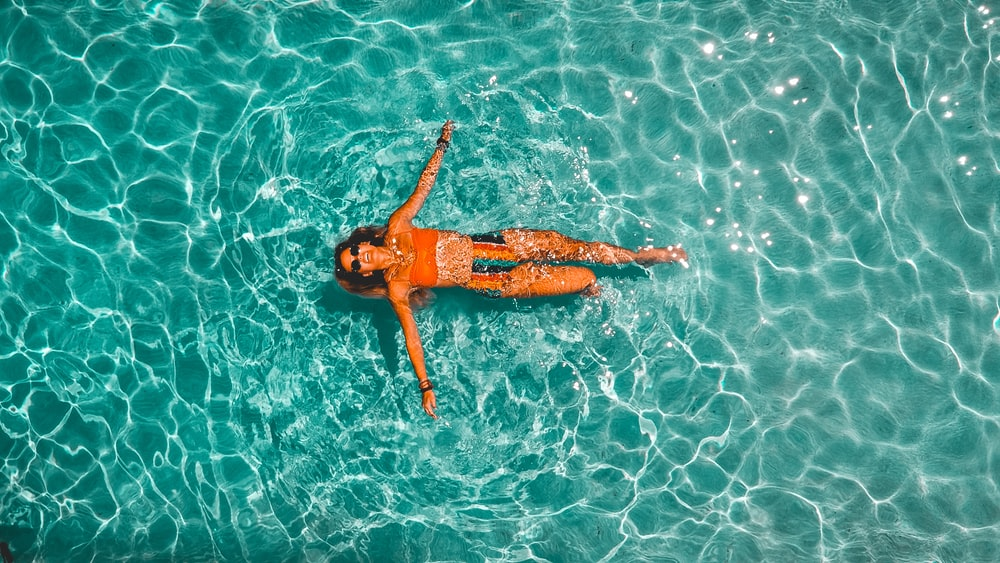 woman swimming alone in body of water
