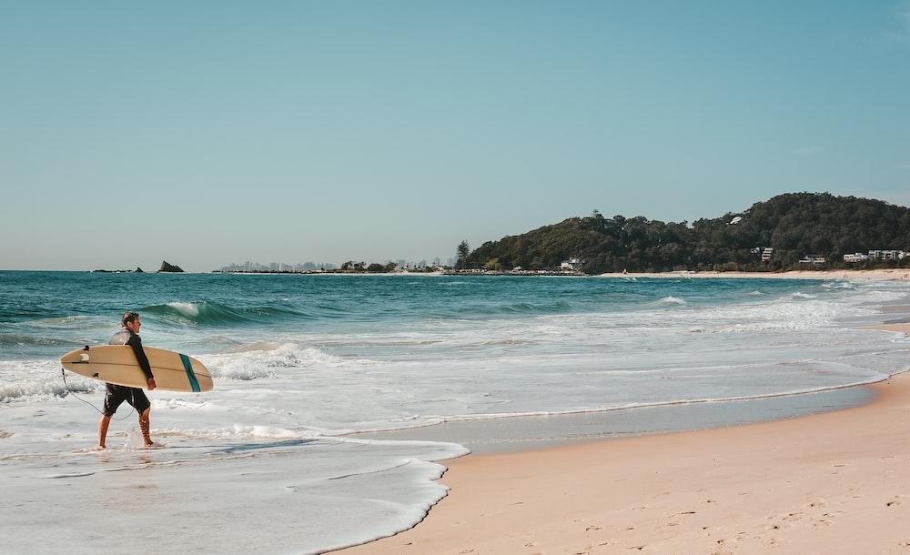 man holding white 2-fin surfboard walking on seashore