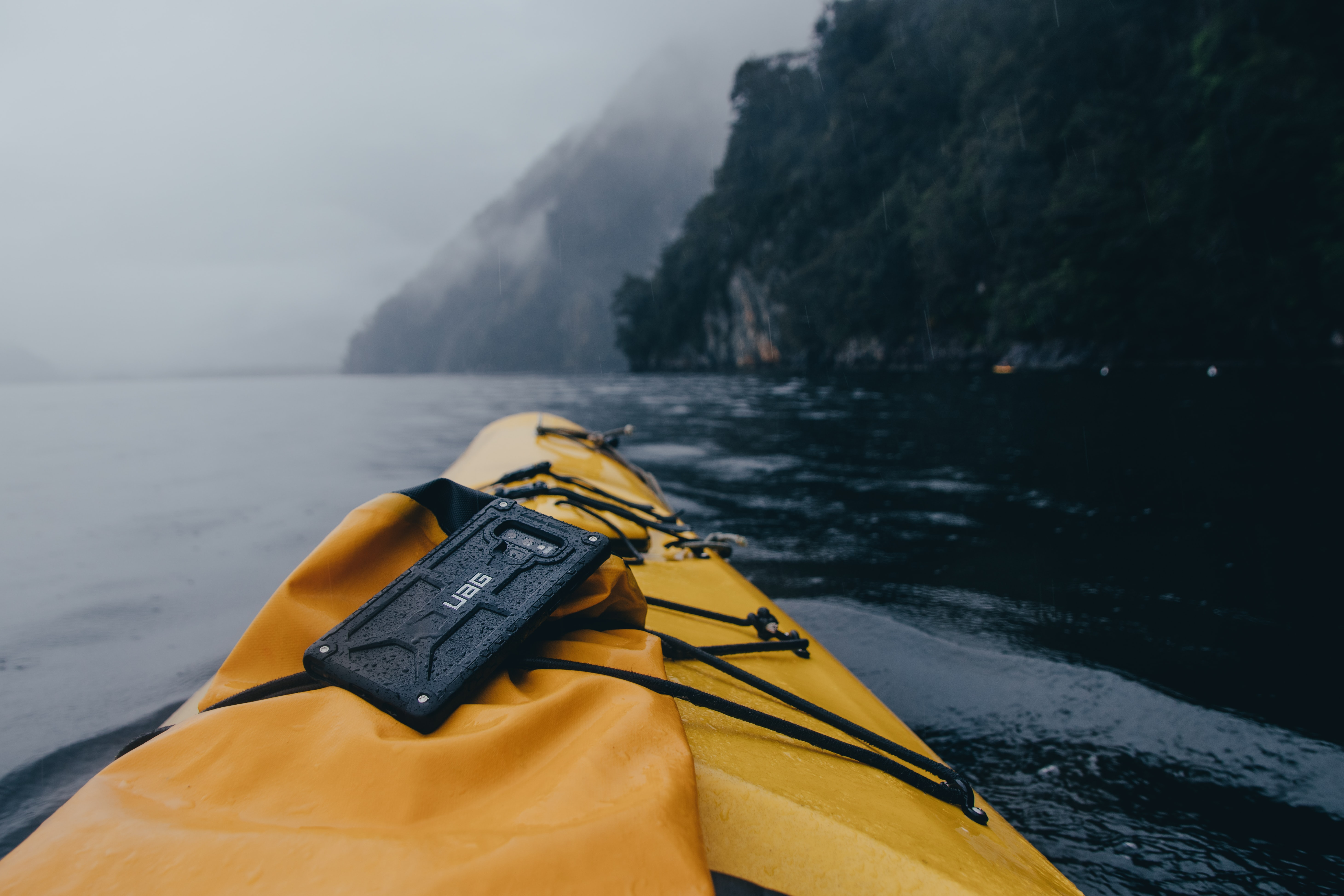 black smartphone with case on yellow kayak on water during daytime