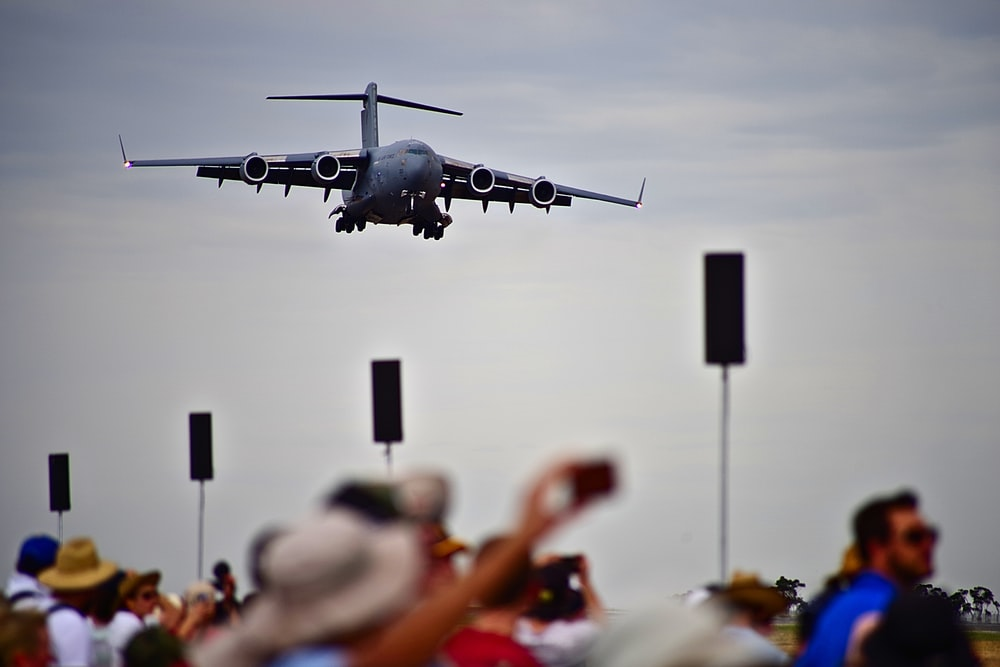 black plane above people watching