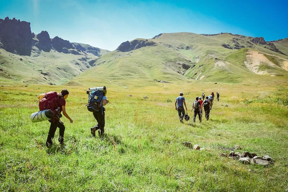people walking on green field near mountains