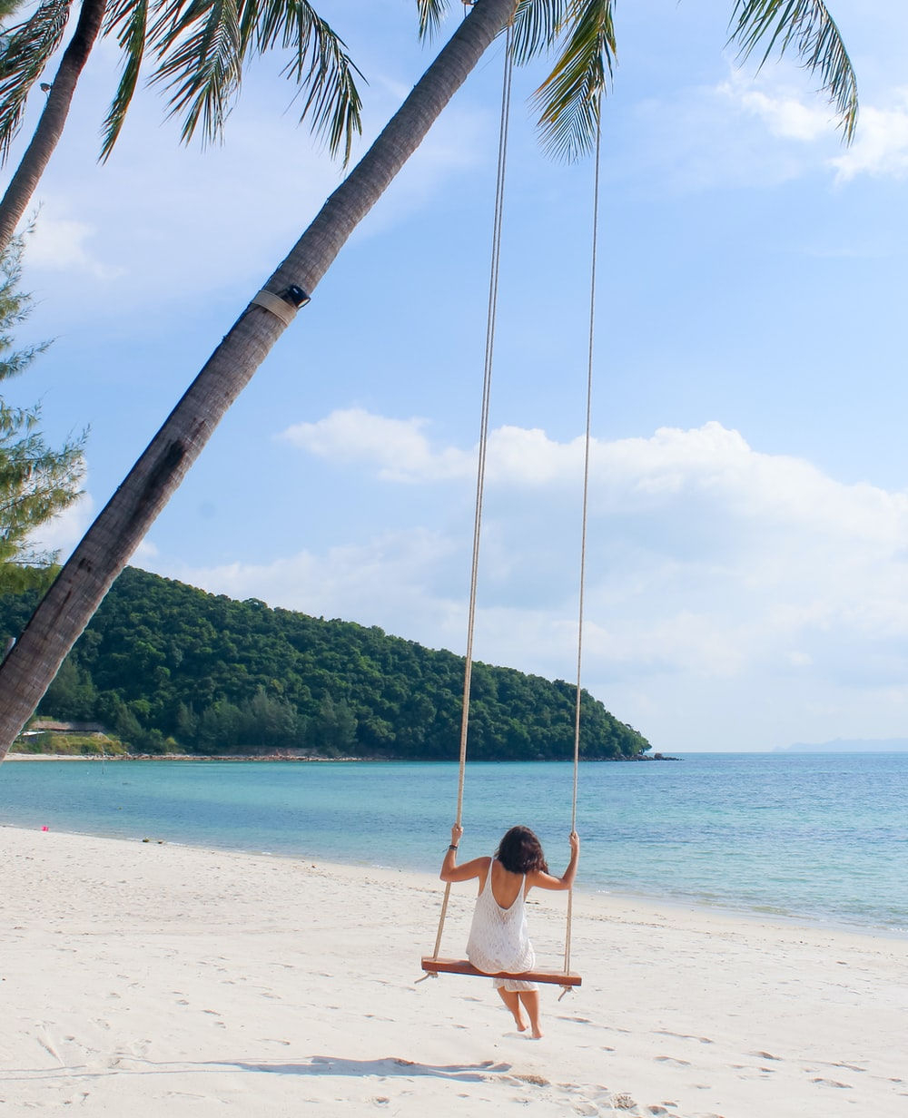 woman wearing white dress sitting on the swing
