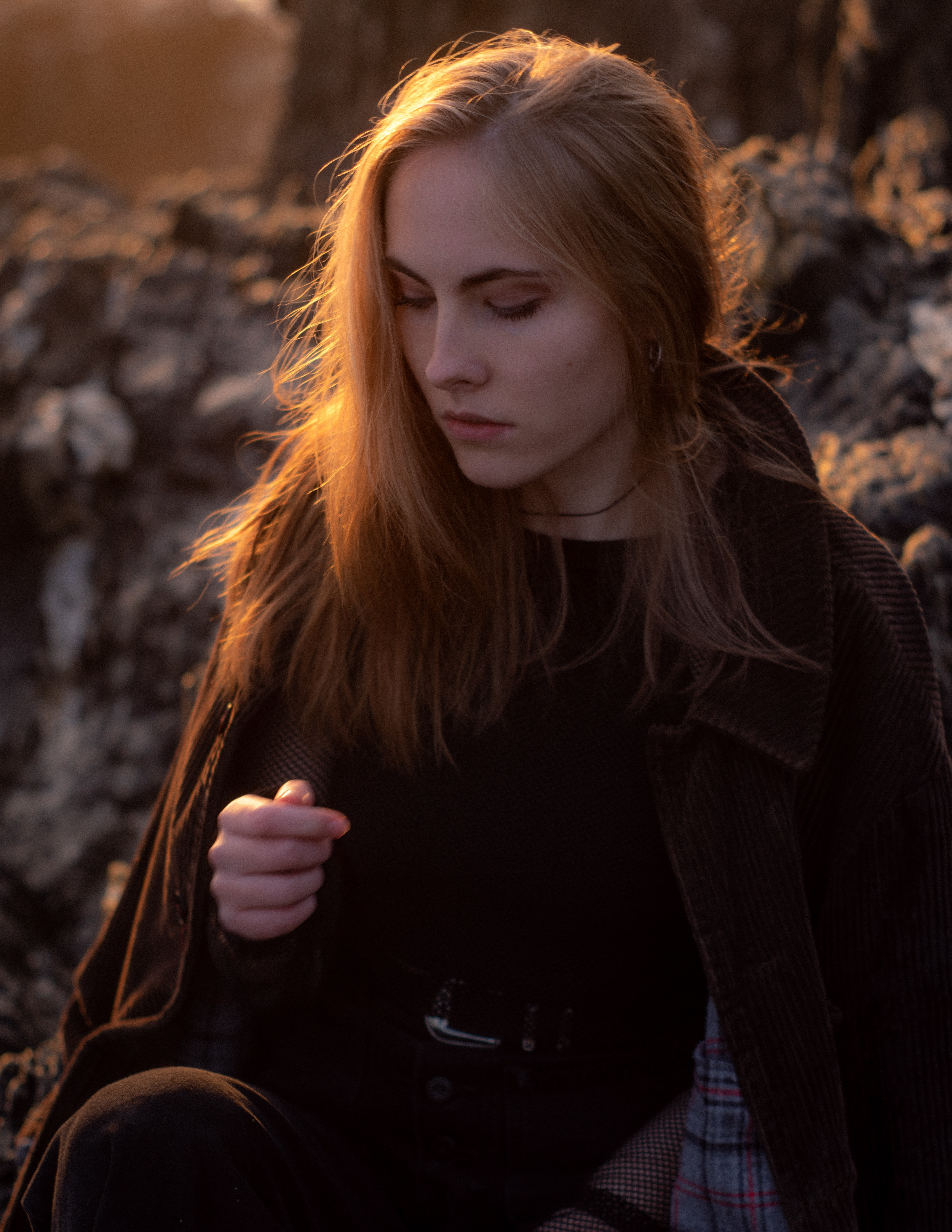 woman wearing brown jacket sitting on rock during golden hour