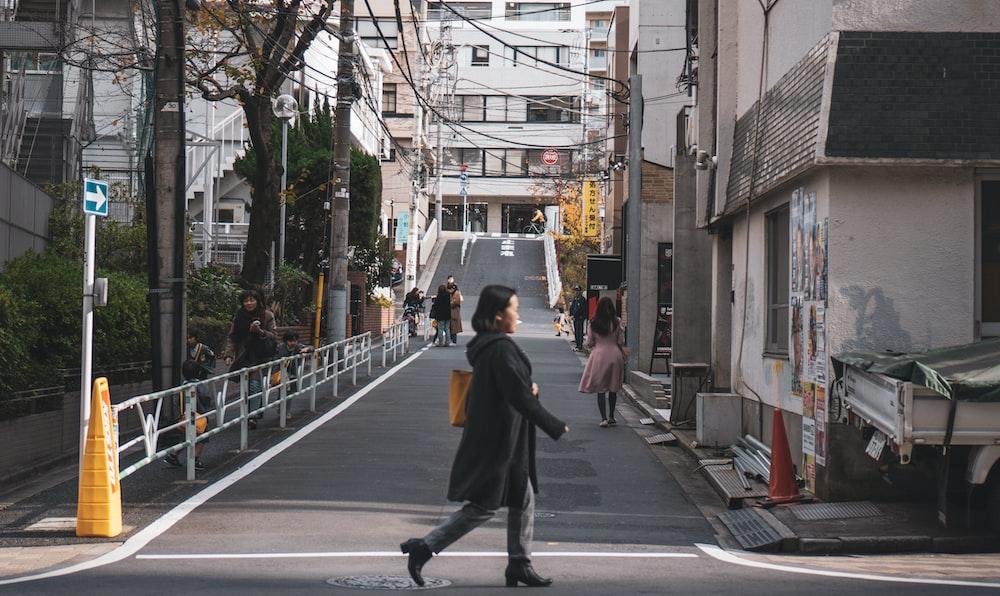 woman in black coat walking in road