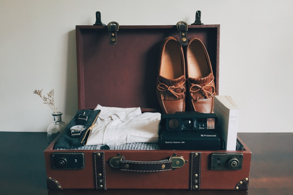 boat shoes inside brown wooden suitcase