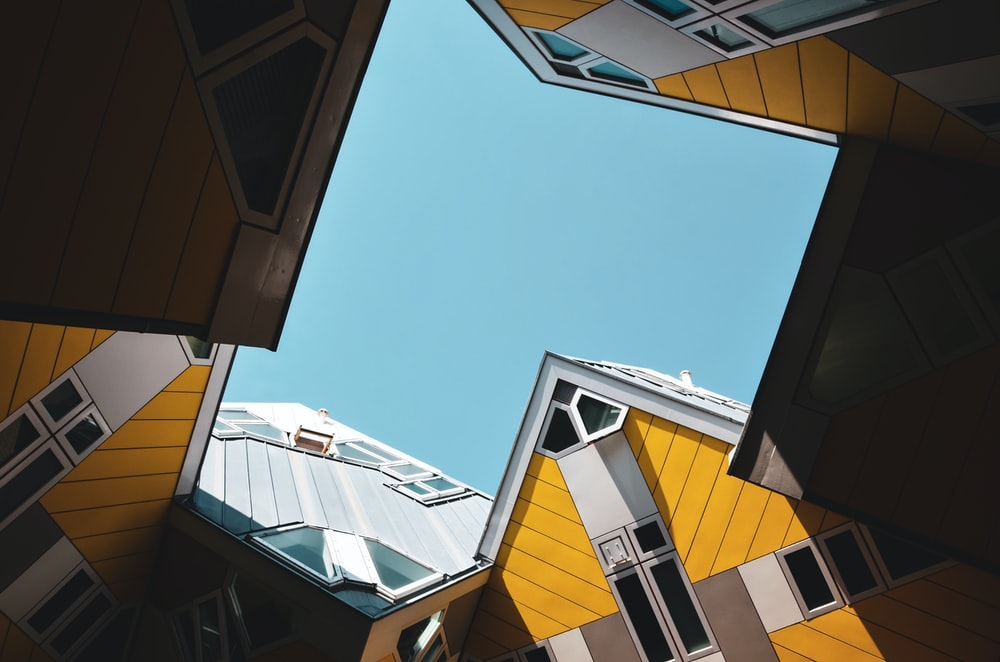 low-angle photography of buildings under calm blue sky
