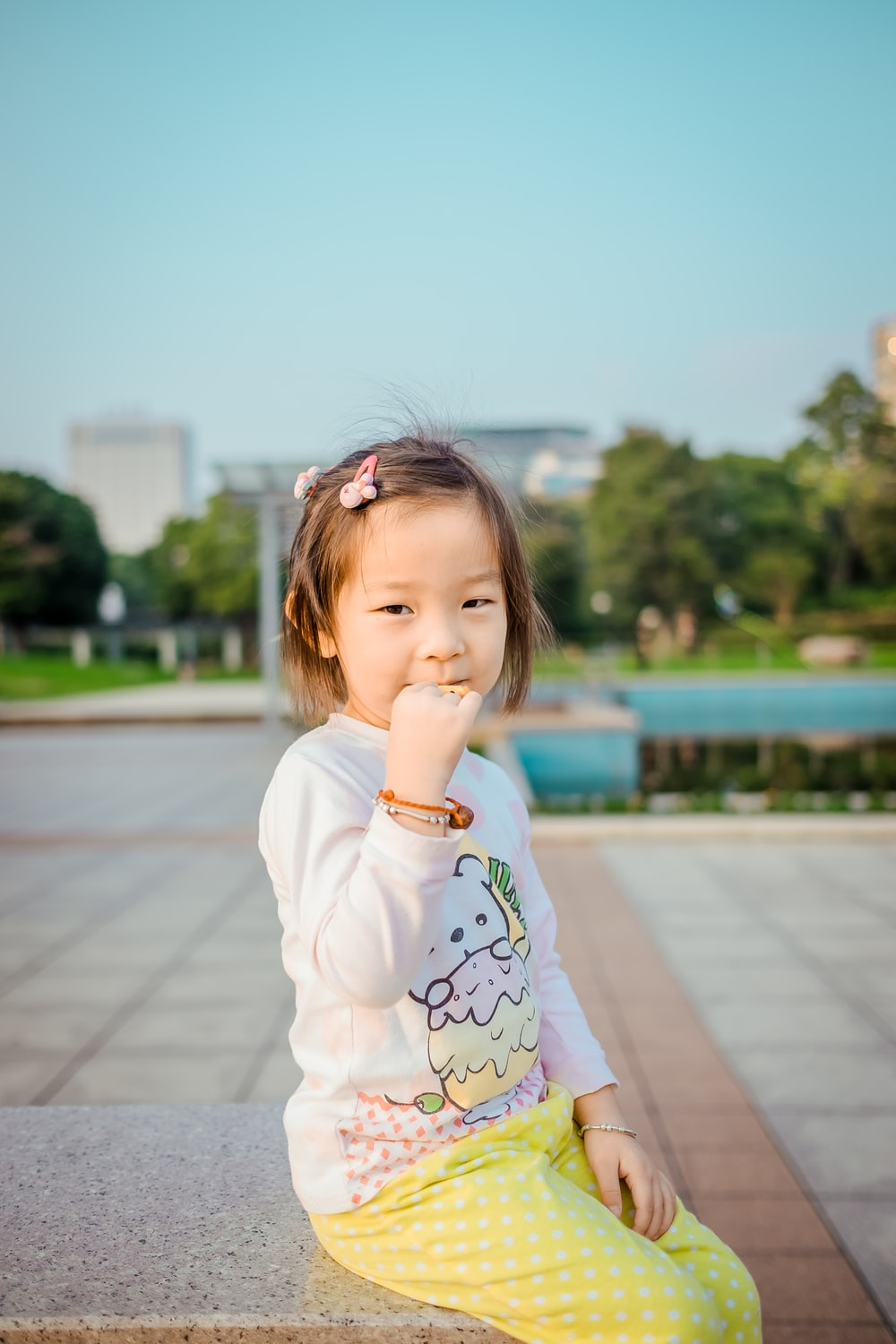 girl sitting while biting her right hand