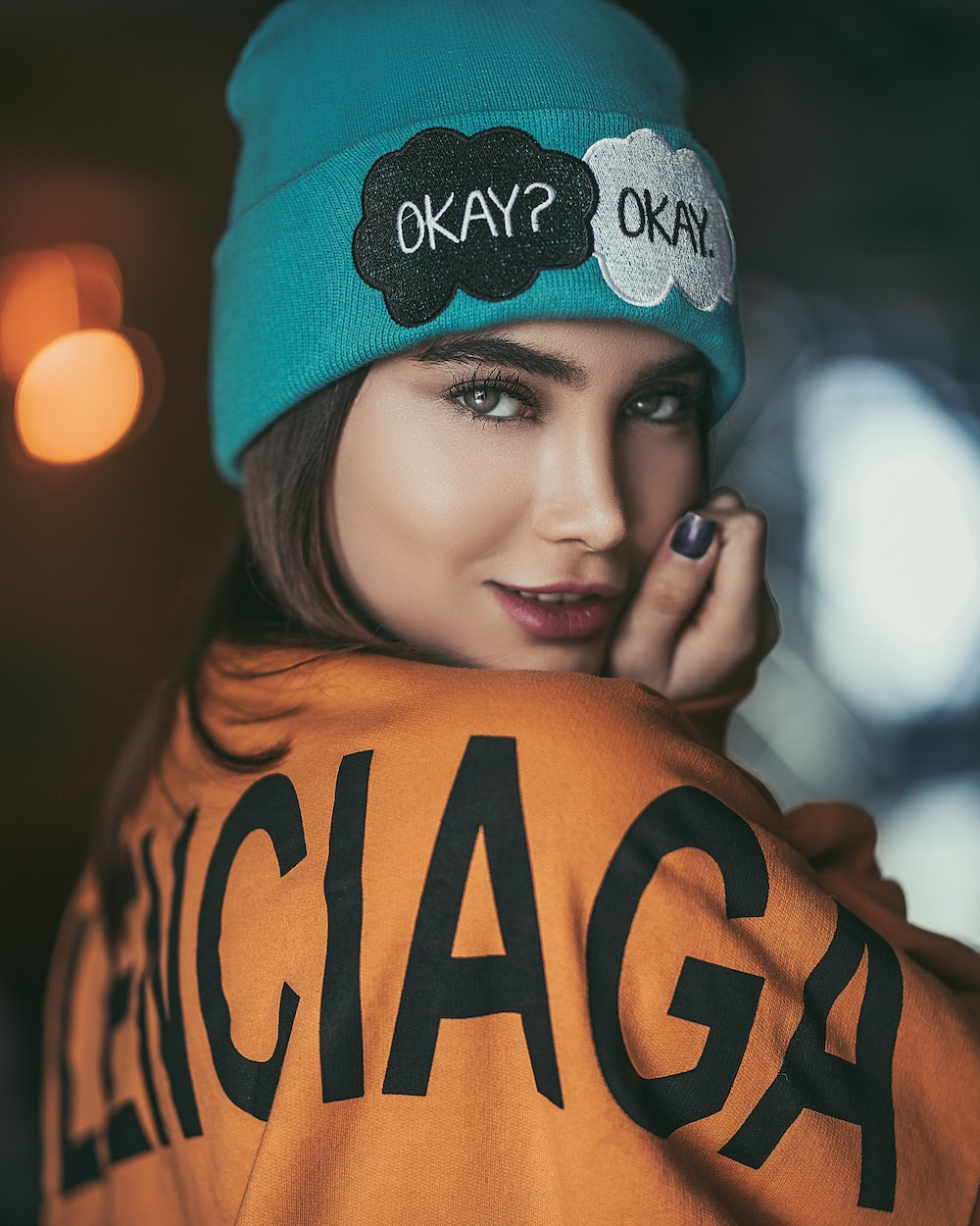 woman wearing orange and black sweater and teal beanie smiling