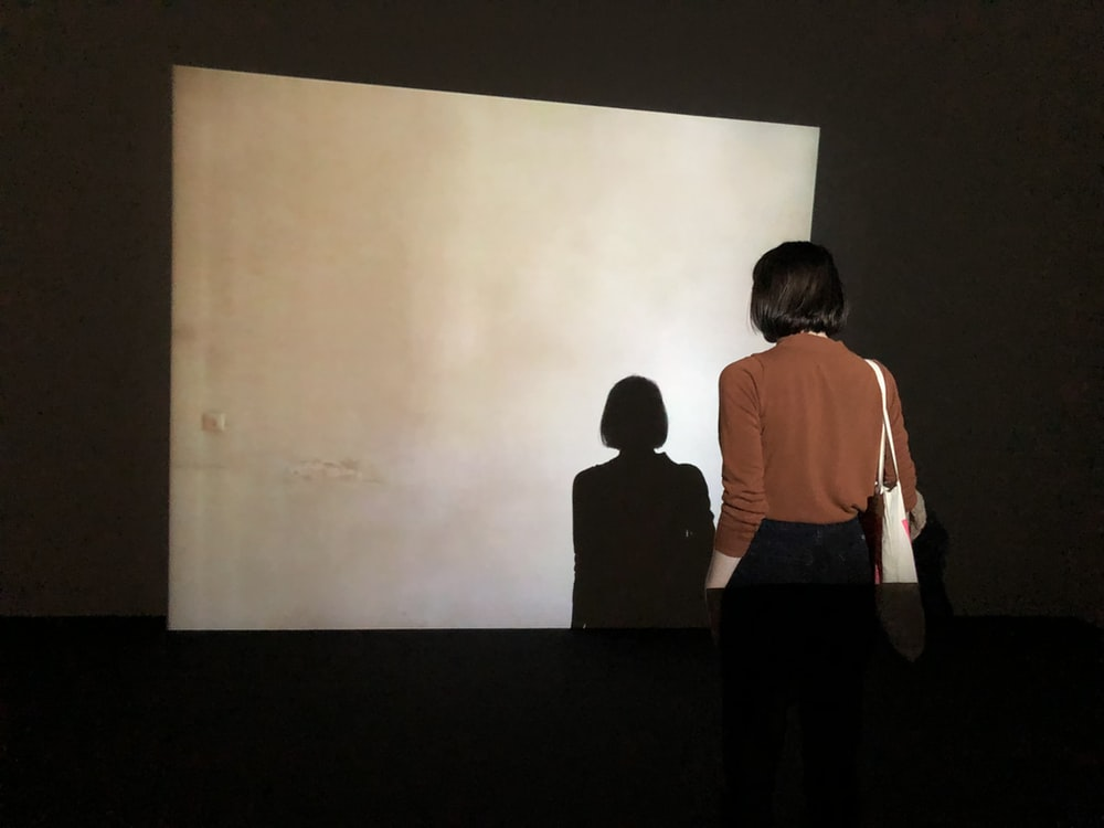 woman facing beige concrete wall with her shadow projected by the light