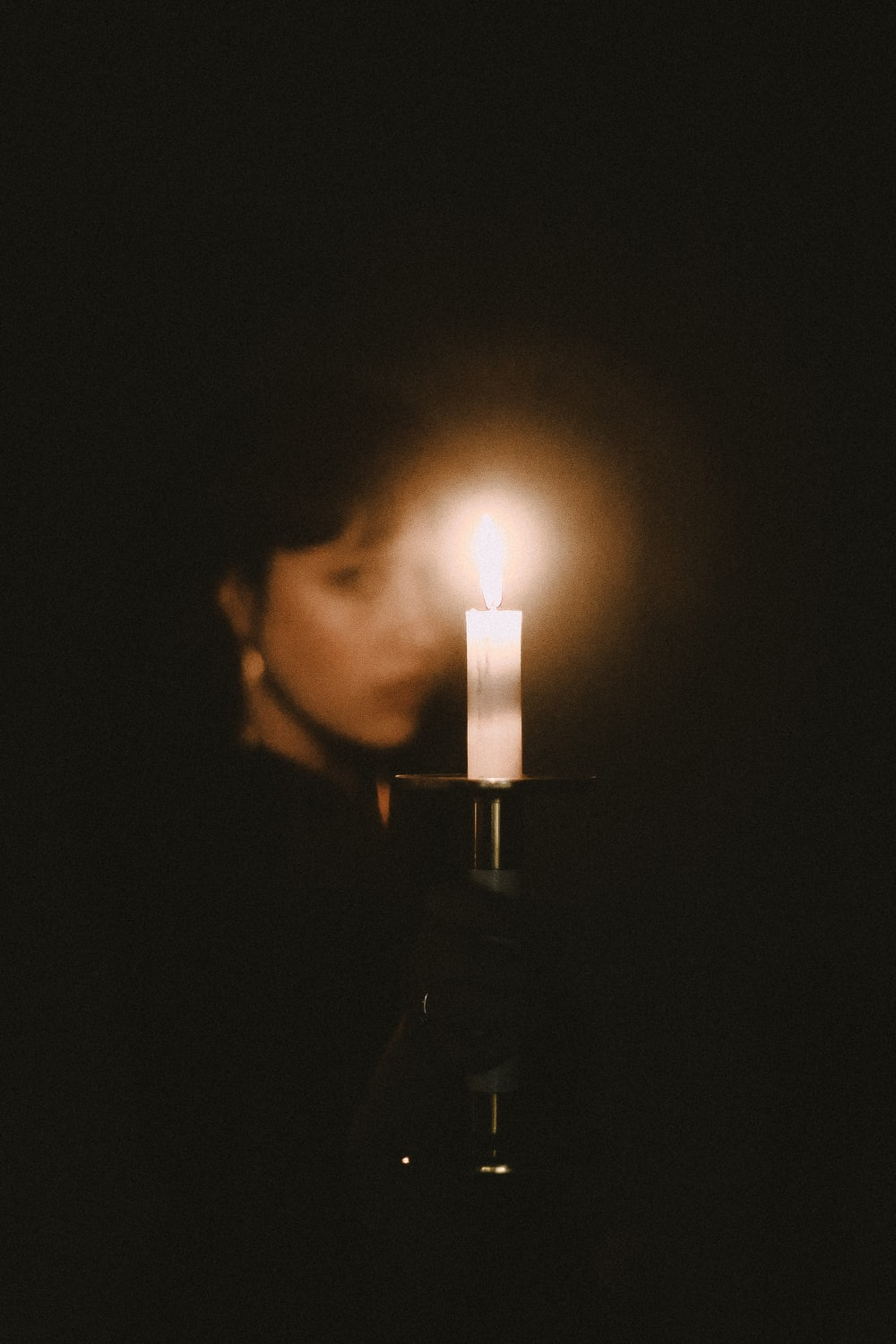 woman holding lit candle on grey candle holder