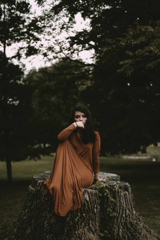 woman sitting on cut tree near trees