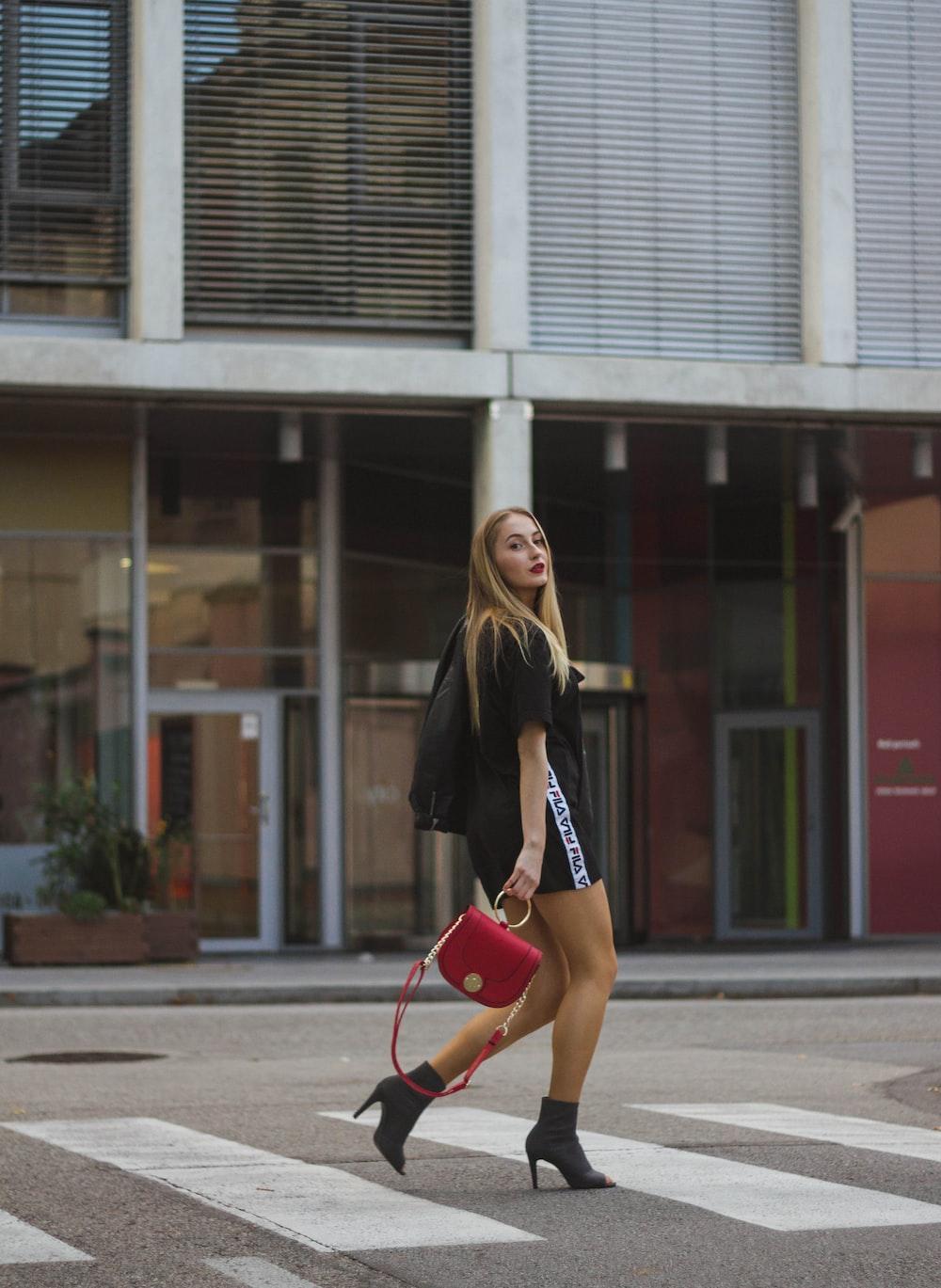 woman in black shirt walking beside white building